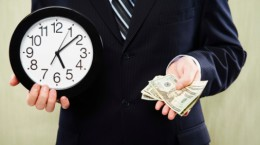 Businessman holding clock and money